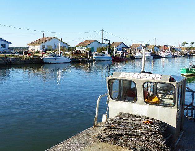 Vue des cabanes du port ostréicole d'Arès à marée haute, avec une plate, bateau utilisé par les ostréiculteurs.