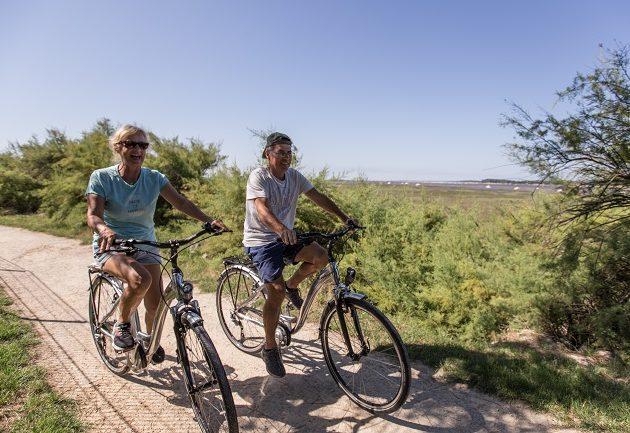 Balade à vélo sur un sentier qui longe le bassin, entre la jetée et le port ostréicole d'Arès.