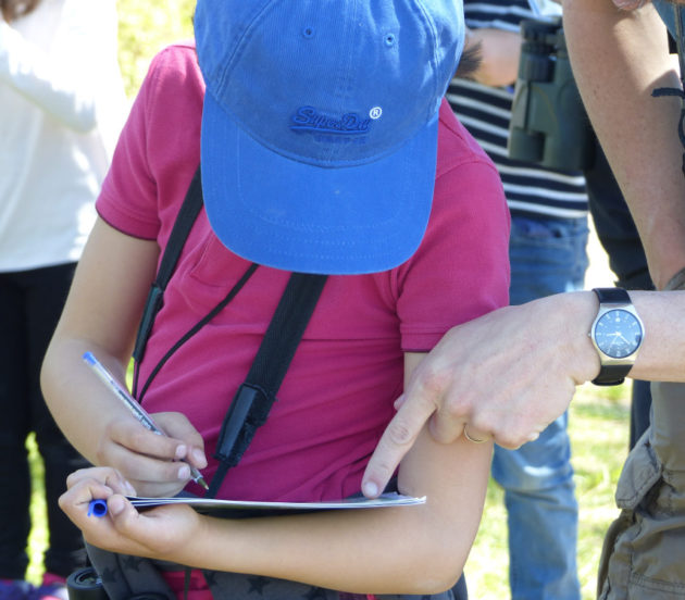 Enfant remplissant son carnet lors de la sortie naturaliste en herbe à Arès