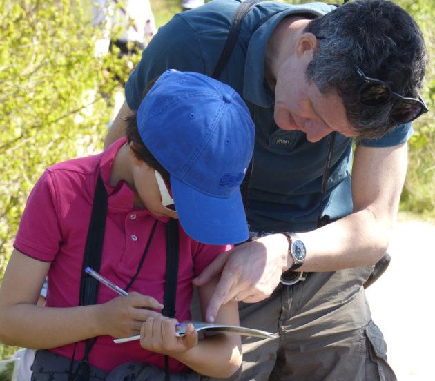 Parent aidant son enfant lors de la sortie naturaliste en herbe à Arès