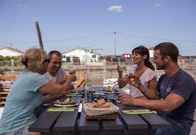 Dégustation d'huîtres à la cabane, entre amis, sur le port ostréicole.